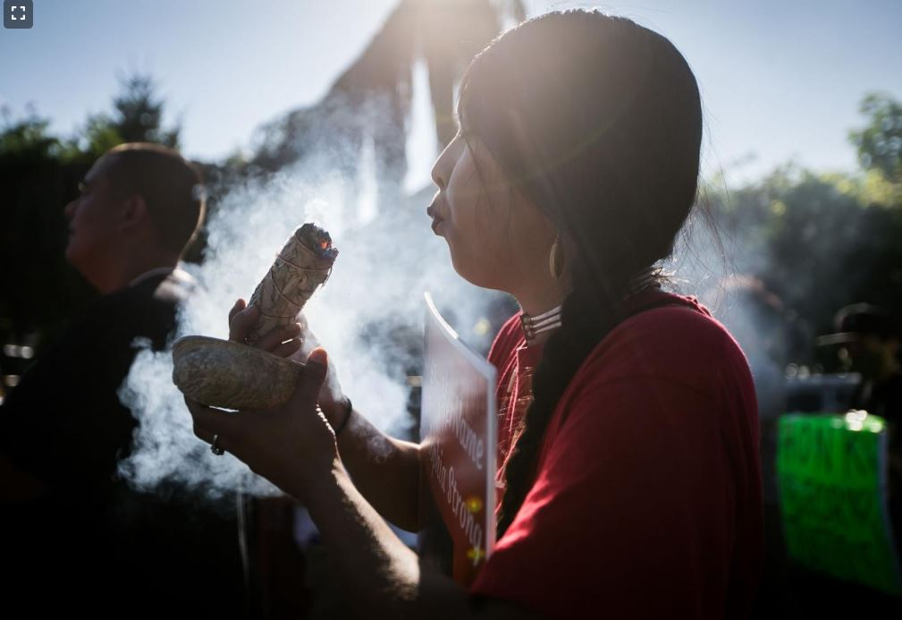 Gabrielle Colfax burns sage during a prayer walk dedicated to missing and murdered Indigenous people Wednesday, July 14, 2021, on South Camas Avenue in Wapato, Wash.  Amanda Ray / Yakima Herald-Republic